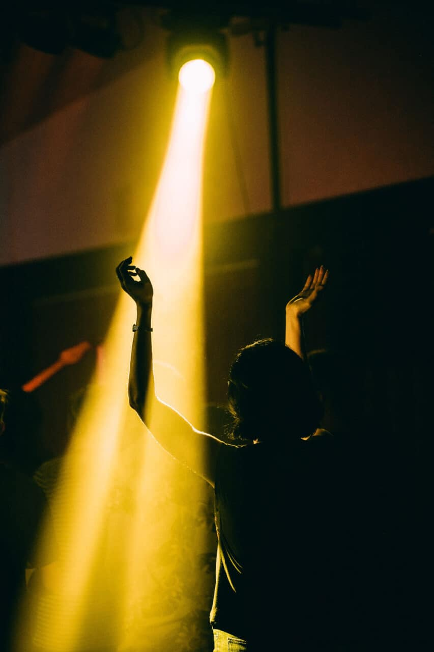 A figure stands in a spotlight with their arms raised